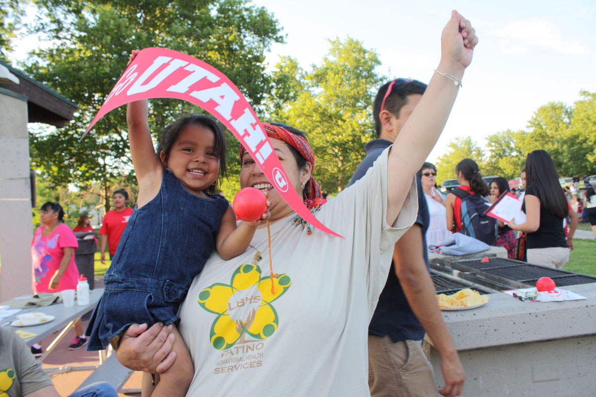 Photo of young girl waving Go Utah pennant