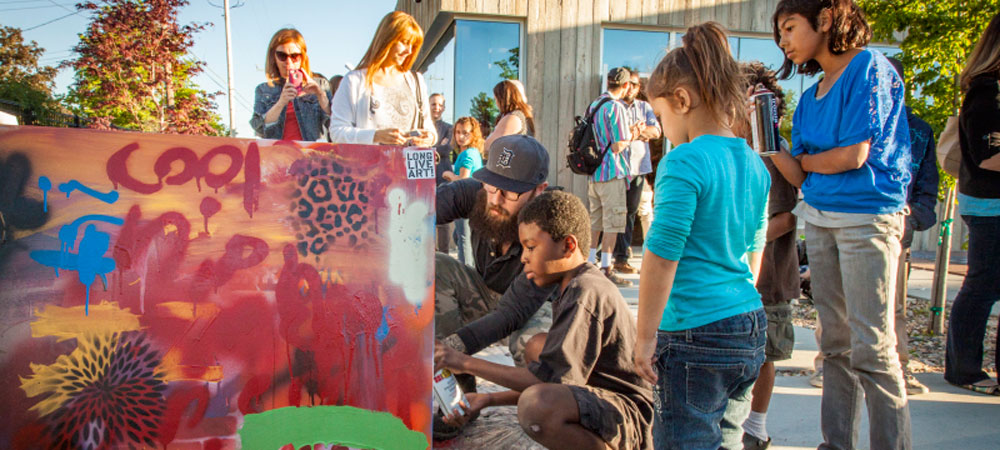 Youth learning to paint graffiti on a board